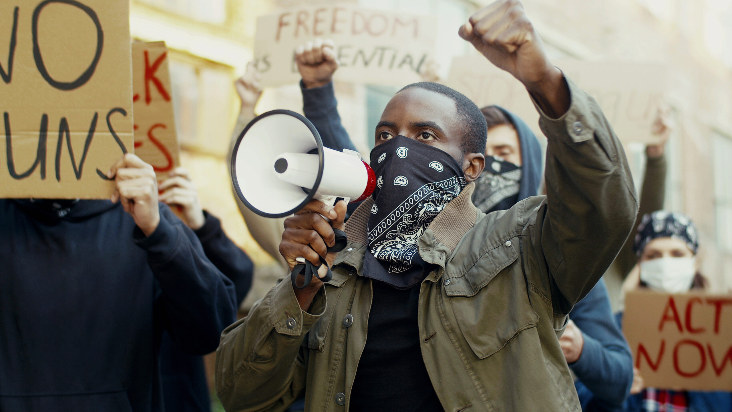 Adobe Stock African American young handsome man in scarf on face like mask screaming in megaphone at protest for human rights outdoors. Group of people protesting at street