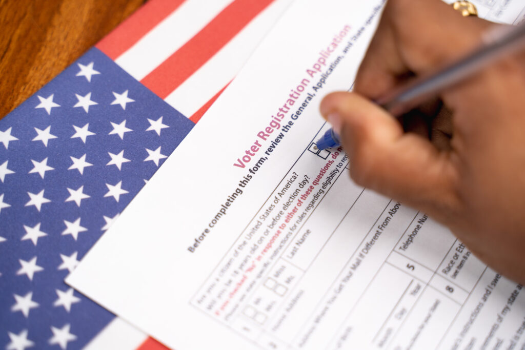 Close up of hands filling President voter Registration Application with US flag as background for upcoming election.